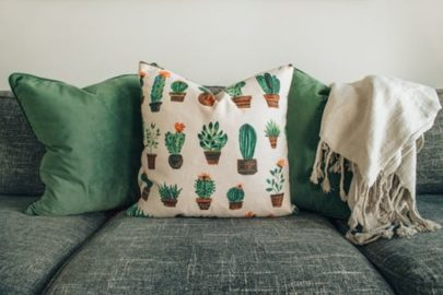 View of grey sofa with green and cactus print cushions created by upholstery Edinburgh expert.