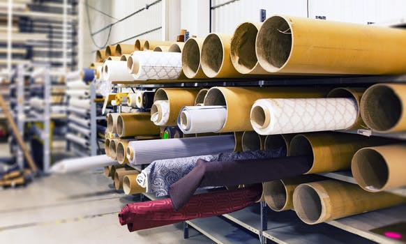 View inside an upholstery Edinburgh workshop with large rolls of fabric piled up on shelves.